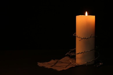Fabric with star of David, barbed wire and burning candle on black background, space for text. Holocaust memory day