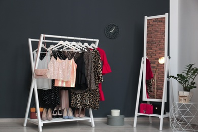 Wardrobe rack with women's clothes and shoes in dressing room