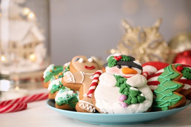 Sweet Christmas cookies on white table against blurred festive lights, closeup