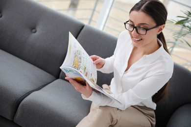 Happy woman reading magazine on sofa in office
