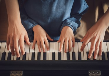 Young woman with child playing piano, above view. Music lesson