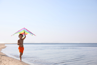 Cute little child with kite running at beach on sunny day