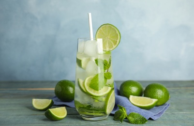 Delicious mojito and ingredients on blue wooden table