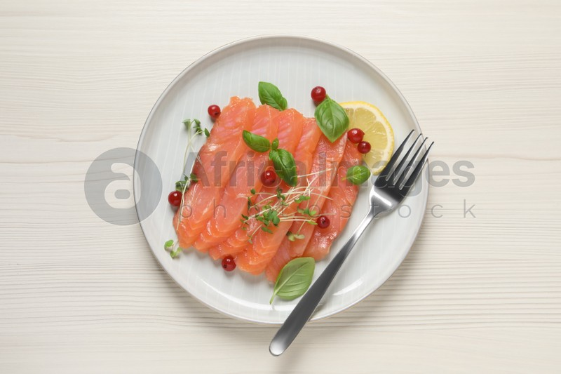 Delicious salmon carpaccio served on white wooden table, top view