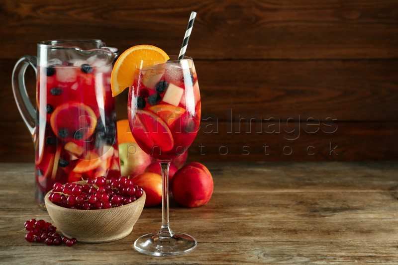 Glass and jug of Red Sangria with fruits on wooden table. Space for text