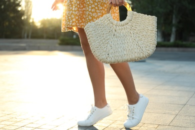 Young woman with stylish straw bag outdoors, closeup