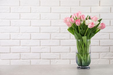 Beautiful bouquet of tulips in glass vase on light table. Space for text