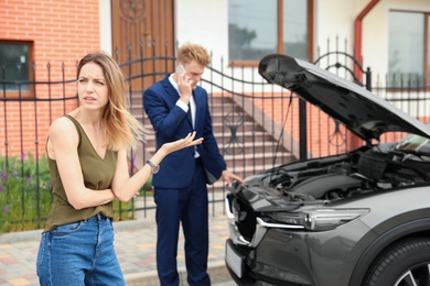 Young man and woman near broken car outdoors