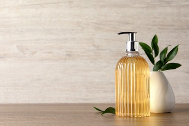Stylish dispenser with liquid soap and green leaves in vase on wooden table, space for text