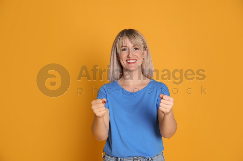 Happy woman pretending to drive car on yellow background