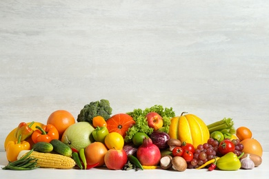 Assortment of fresh organic fruits and vegetables on light table. Space for text