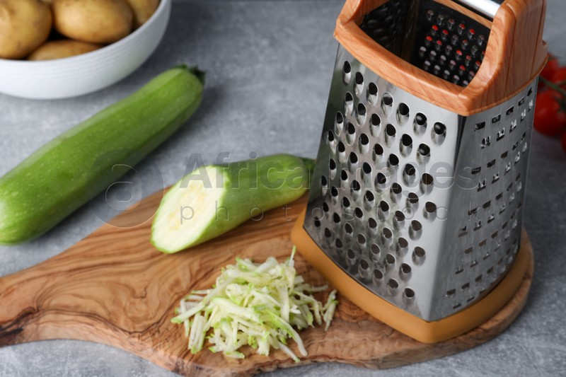 Grater and fresh zucchinis on grey table