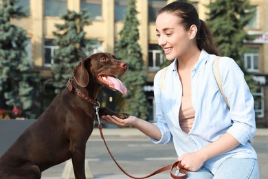 Young woman with her German Shorthaired Pointer dog on city street