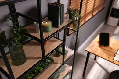 Shelving with different decor, books and houseplants near gray wall in room. Interior design