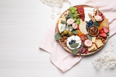 Assorted appetizers served on white wooden table, flat lay. Space for text