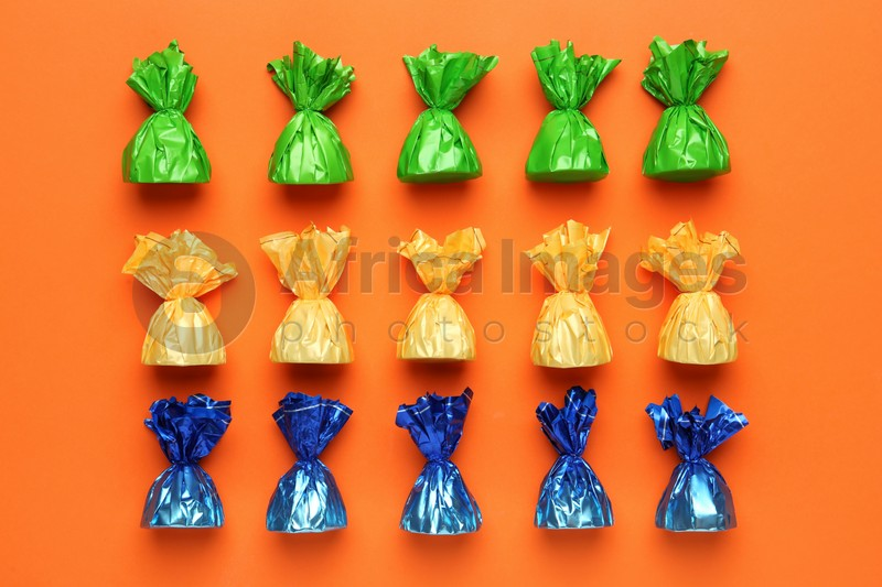 Many candies in colorful wrappers on orange background, flat lay