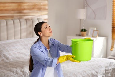 Young woman collecting leaking water from ceiling in bedroom. Time to call roof repair service