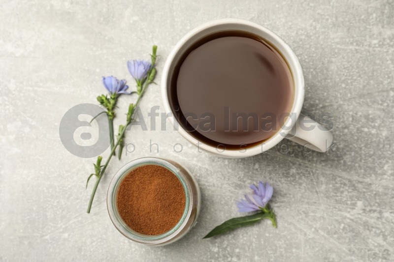 Cup of delicious chicory drink, powder and flowers on light grey table, flat lay