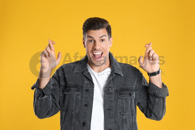 Man with crossed fingers on yellow background. Superstition concept