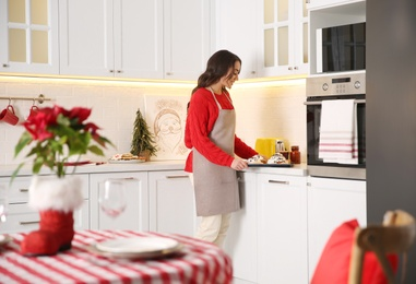 Young woman with sweet buns for Christmas dinner in kitchen
