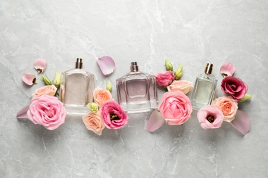 Flat lay composition of different perfume bottles and flowers on light grey marble background