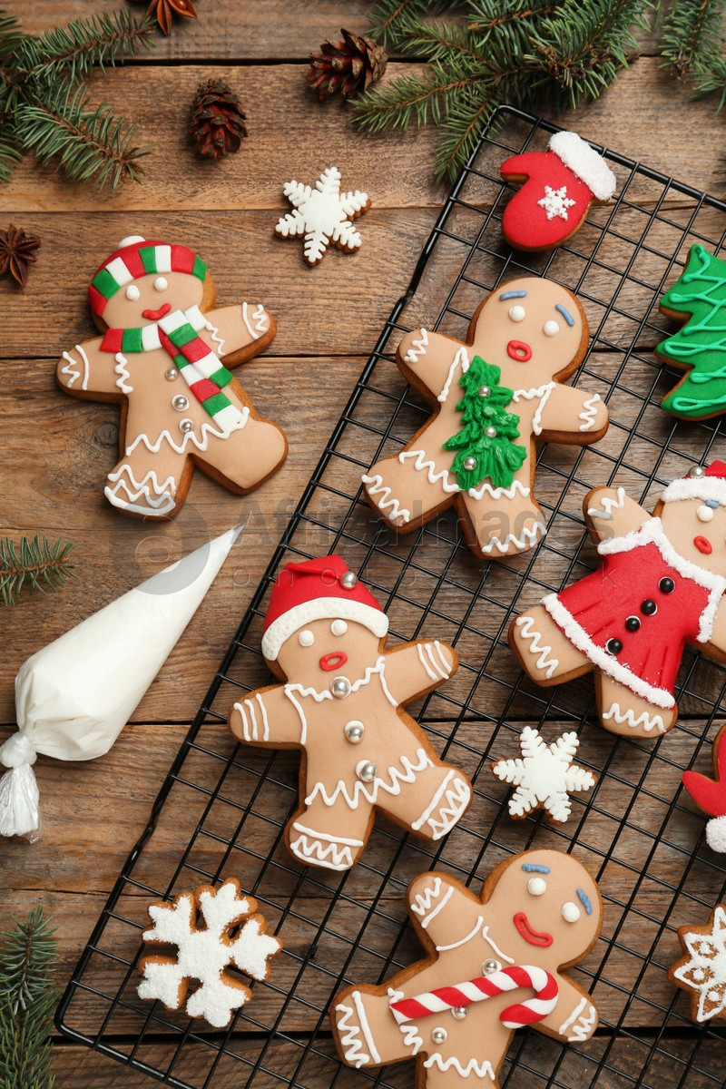 Delicious Christmas cookies and fir branches on wooden table, flat lay