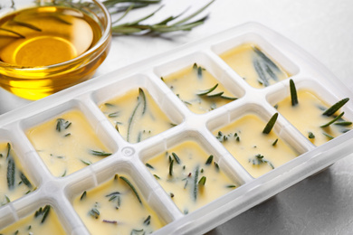 Ice cube tray with herbs frozen in oil and fresh rosemary on grey table, closeup