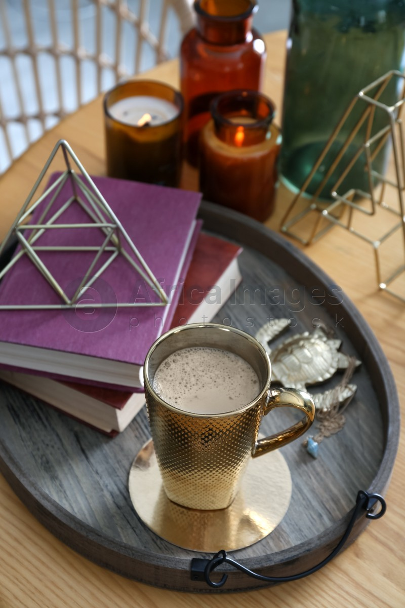 Wooden tray with decorations, books and hot drink on table