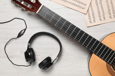 Composition with guitar and music notations on light wooden table, flat lay