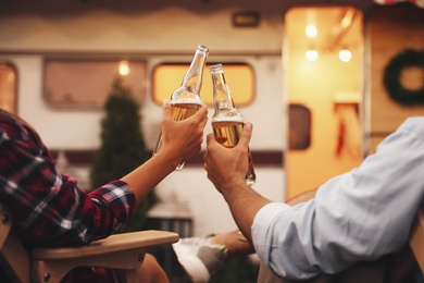 Young couple toasting with bottles of beer near trailer, closeup. Camping season