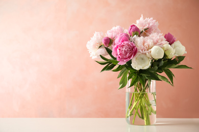 Beautiful peony bouquet in vase on table against pink background. Space for text