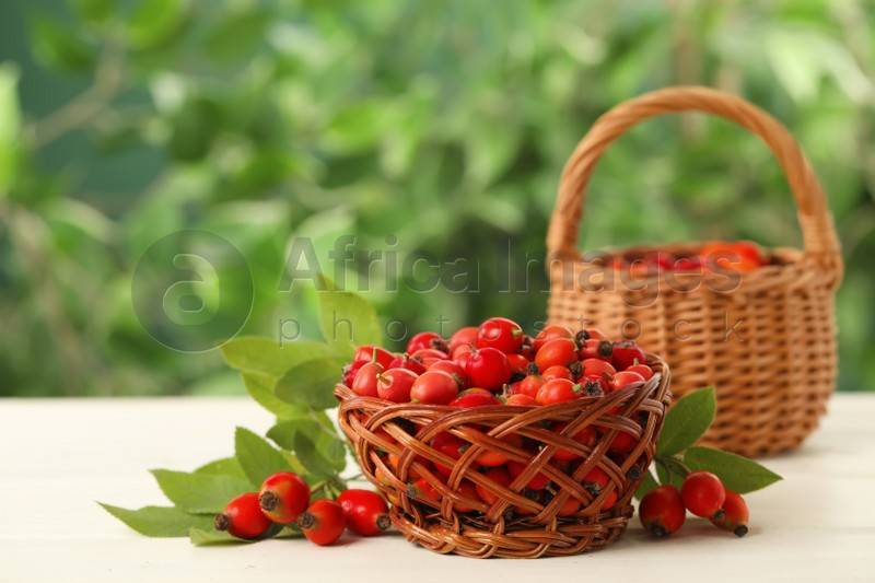 Ripe rose hip berries with green leaves on white wooden table outdoors
