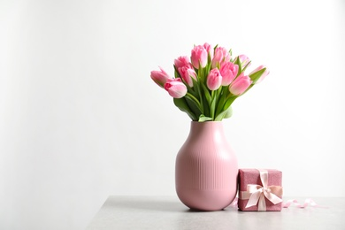 Bouquet of beautiful spring tulips in vase and gift box on table against white background. International Women's Day