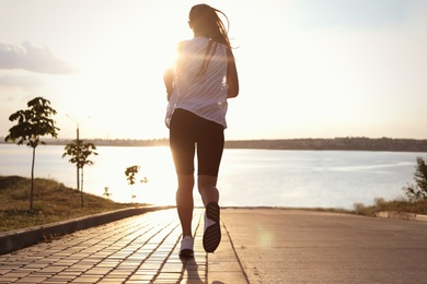 Young woman running near river in morning, back view