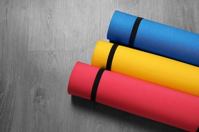 Bright rolled camping mats on grey wooden background