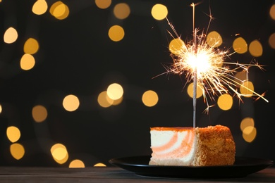 Cake with burning sparkler on black table against blurred festive lights. Space for text
