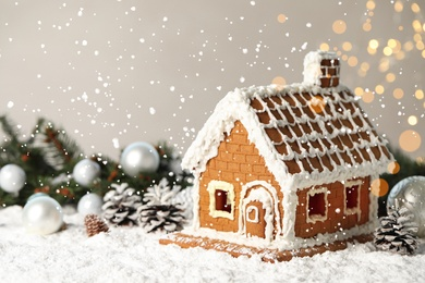 Beautiful gingerbread house decorated with icing on snow, space for text