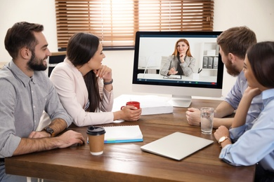 Team of coworkers having video chat with boss in office