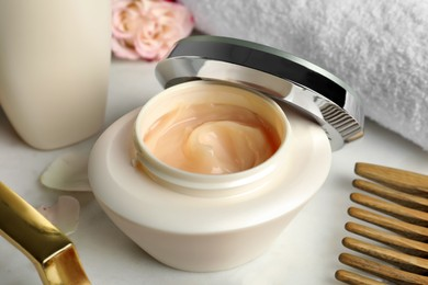 Open jar of hair care cosmetic product on white table