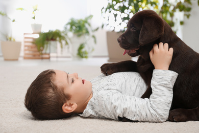 Little boy with dog lying on floor at home