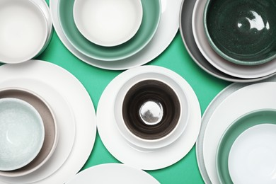 Different plates and bowls on green background, flat lay