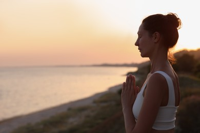 Mature woman meditating near sea in evening. Space for text