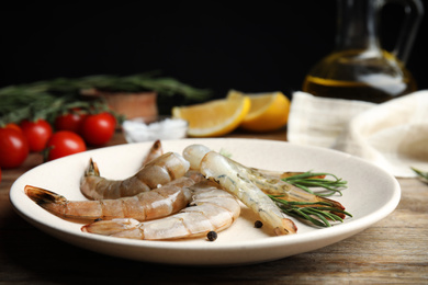 Fresh raw shrimps with rosemary and pepper on wooden table