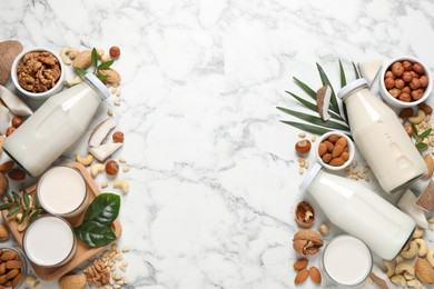Vegan milk and different nuts on white marble table, flat lay. Space for text