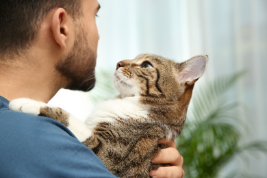 Happy man with cat at home, closeup. Friendly pet