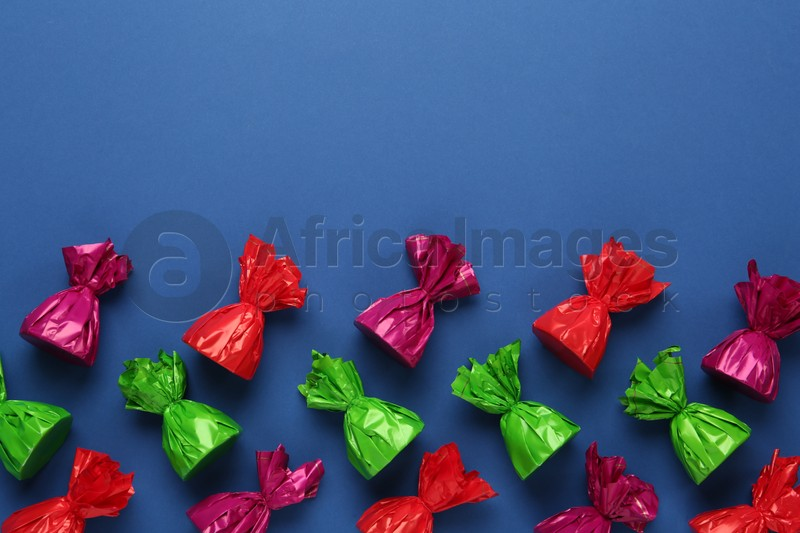 Many candies in colorful wrappers on blue background, flat lay. Space for text