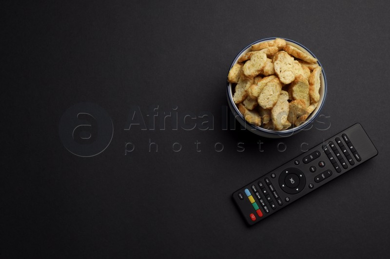 Modern tv remote control and rusks on black background, flat lay. Space for text