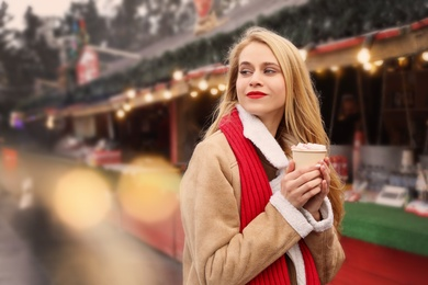 Young woman with hot drink at Christmas fair