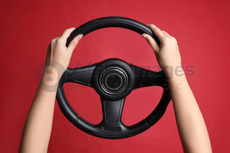 Woman holding steering wheel on red background, closeup