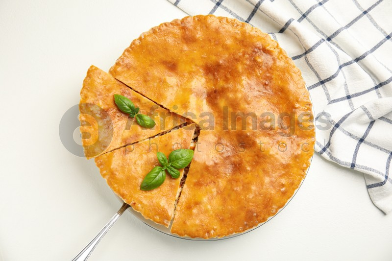 Delicious pie with meat and basil on white table, flat lay